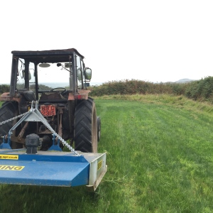tractor and topper in field